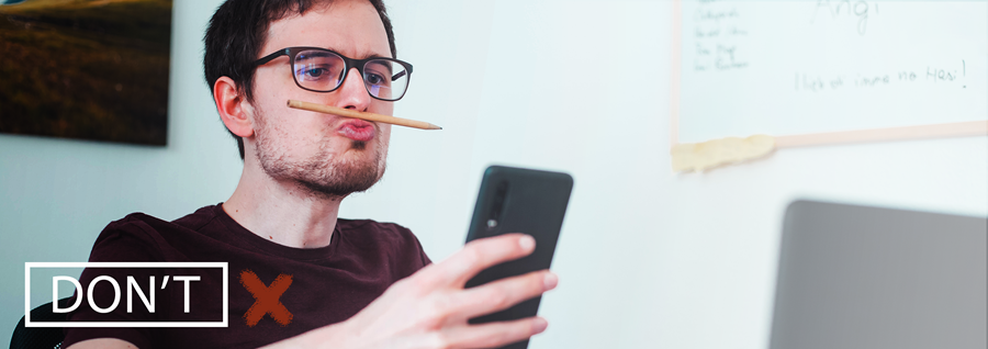 Man is playfully looking at his phone while balancing a pencil between his lips and nose.