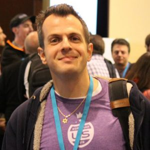Web Developer Andy Stitt smiling in a crowed of people.