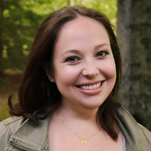 Chief Collaboration Officer, Sarah Denison smiling outside in a wooded area.